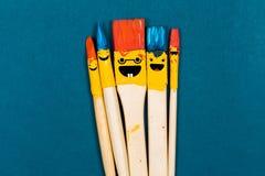 Cinco cepillos de la sonrisa en el papel azul imagen de archivo