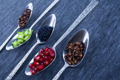 Cinco colheres com alimento e especiarias Fotos de Stock Royalty Free