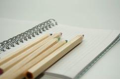 Cinco colorearon los lápices de madera en el fondo de una hoja en blanco de la libreta foto de archivo libre de regalías