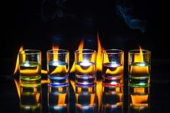 Cinco coloridos completamente de vidros de tiro das bebidas refletiram no g fotos de stock royalty free