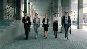 Cinco compañeros de trabajo del negocio que caminan hacia hablar amistoso del centro de negocios el uno al otro almacen de metraje de vídeo