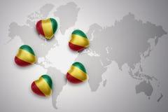 cinco corazones con la bandera nacional de Guinea en un fondo del mapa del mundo Imagen de archivo libre de regalías