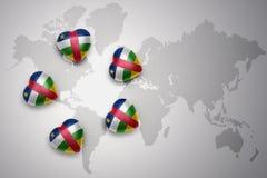 Cinco corazones con la bandera nacional de la República Centroafricana en un fondo del mapa del mundo Fotografía de archivo