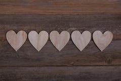 Cinco corazones de madera en fila en un fondo de madera imagenes de archivo