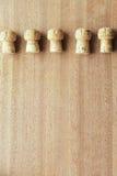 Cinco corchos del roble de corcho del champán alinearon en fila encima del tablero de madera Imagen de archivo