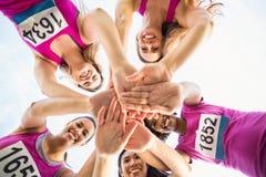 Cinco corredores sonrientes que apoyan maratón del cáncer de pecho foto de archivo