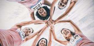 Cinco corredores sonrientes que apoyan maratón del cáncer de pecho fotografía de archivo