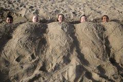 Cinco crianças caucasianos felizes bonitos enterradas na areia no bea imagem de stock royalty free