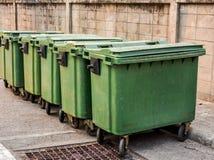 Cinco cubos de la basura verdes en los rodillos Foto de archivo libre de regalías