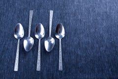 Cinco cucharas de plata con el modelo Fotos de archivo libres de regalías