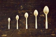 Cinco cucharas en la tabla imagen de archivo