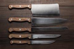 Cuchillos de cocina sobre la tabla de madera marrón Foto de archivo libre de regalías