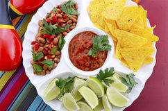 Cinco de Mayo bright colorful party food. Happy Cinco de Mayo bright colorful party food with chilli beans, corn chips, salsa and limes platter on red wood Royalty Free Stock Photo