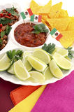 Cinco de Mayo bright colorful party food. Happy Cinco de Mayo bright colorful party food with chilli beans, corn chips, salsa and limes platter on red wood Royalty Free Stock Photos