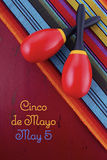 Cinco de Mayo concept with maracas on Mexican style fabric. Happy Cinco de Mayo concept with maracas on Mexican style fabric on red wood distressed table Stock Images