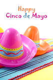 Cinco de Mayo festive sombrero hats. Close up on festive decorated table against a white background, with greeting text