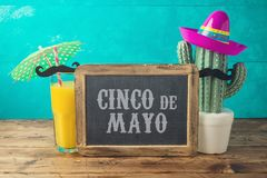 Cinco de Mayo holiday background with chalkboard, Mexican cactus, party sombrero hat and orange juice. On wooden table royalty free stock images
