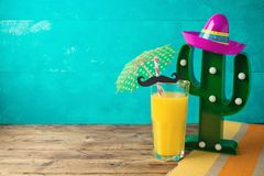 Cinco de Mayo holiday background with Mexican cactus, party sombrero hat and orange juice. On wooden table royalty free stock image