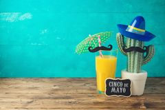 Cinco de Mayo holiday background with Mexican cactus, party sombrero hat and orange juice. On wooden table royalty free stock photos