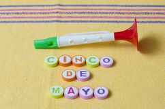 Cinco de mayo made from colorful letters and toy trumpet. On yellow tablecloth