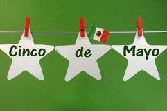 Cinco de Mayo message greeting written across white stars and Mexico flag hanging pegs on a line Stock Photos