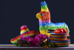 Cinco de Mayo Party Table. Colorful Happy Cinco de Mayo party table with rainbow straw donkey and sombrero pinata against a black background royalty free stock photos