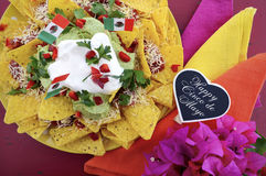 Cinco de Mayo party table with nachos food platter. Happy Cinco de Mayo party table with nachos food platter and bright orange, red, and pink napkins on a red Stock Photography