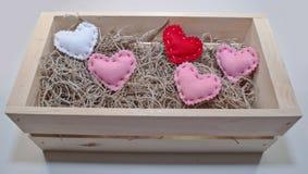 Cinco diversos corazones coloreados del paño en una caja de madera imagen de archivo