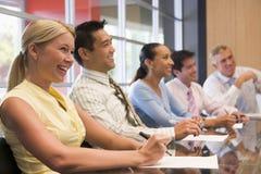 Cinco empresarios en la sonrisa del vector de la sala de reunión Imágenes de archivo libres de regalías
