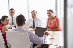 Cinco empresarios que tienen reunión en la sala de reunión Fotografía de archivo libre de regalías