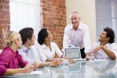 Cinco empresários na sala de reuniões com portátil Imagem de Stock