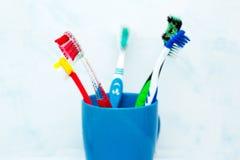 Cinco escovas de dentes no vidro cerâmico imagens de stock