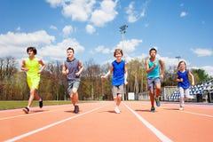 Cinco esprinteres adolescentes que corren junto en una pista Imagen de archivo libre de regalías