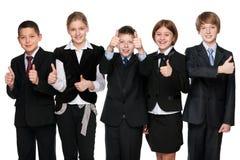 Cinco estudiantes felices detienen sus pulgares Foto de archivo libre de regalías