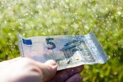 Cinco euros en una lluvia imagenes de archivo