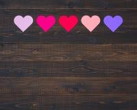 Cinco fieltro Valentine Hearts en diversos colores en fila en tableros de madera rústicos oscuros Imagen de archivo