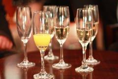 Cinco flautas de champanhe com champanhe e fanfarrões efervescem imagem de stock
