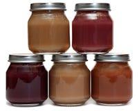 Cinco frascos do comida para bebê e da colher Imagem de Stock Royalty Free