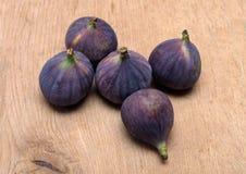 Cinco frutas maduras de los higos en superficie de madera marrón Fotos de archivo libres de regalías