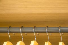 Cinco ganchos em seguido em uma barra cinzenta em um vestuário de madeira Fotos de Stock Royalty Free