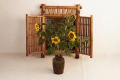 Cinco girasoles en un florero de la arcilla Imagen de archivo