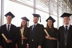 Cinco graduados nos almofarizes e nos vestidos que guardam certificados fotos de stock