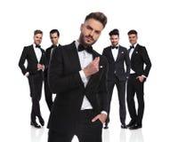Cinco groomsmen elegantes que estão com o líder arrogante na parte dianteira foto de stock royalty free