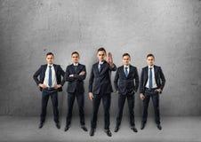 Cinco hombres de negocios llenos-lenght que se colocan en diversas actitudes aisladas en el fondo blanco Foto de archivo libre de regalías