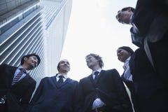 Cinco hombres de negocios que se colocan al aire libre que hablan y sonrientes, Pekín, opinión de ángulo bajo imagenes de archivo
