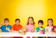 Cinco huevos de Pascua de la pintura de los niños en la tabla Foto de archivo libre de regalías