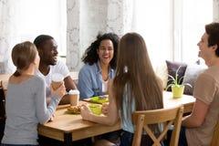 Cinco jovens multirraciais que têm o divertimento que senta-se no café fotografia de stock royalty free