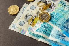 Cinco libras esterlinas novas da nota e uma moeda de libra Fotografia de Stock Royalty Free