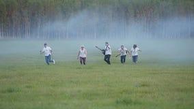 Cinco músicos com os instrumentos que correm através de um campo fumo-enchido Quadro alegre muito fresco vídeos de arquivo