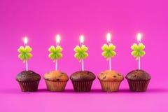 Cinco magdalenas con las velas ardientes sobre un fondo rosado Foto de archivo